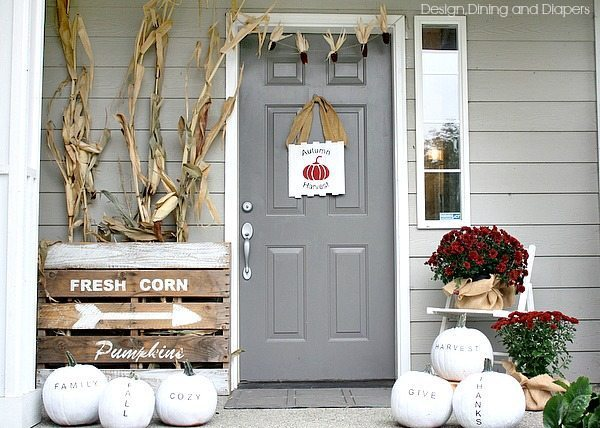 Love this unconventional fall porch decor using white, black and deep red with cornstalks and trendy typography pumpkins!