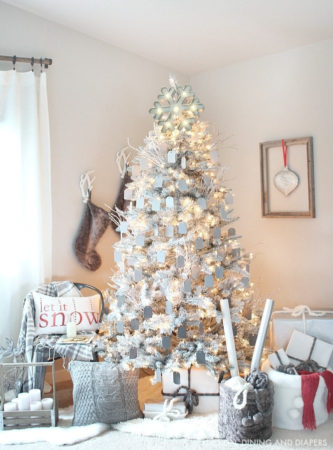Create a magical rustic modern Christmas display using a gray and white Christmas tree and ombre gray ornaments. The pops of red on this Christmas display keep your eye moving and pulls you in. Such a dreamy setting.