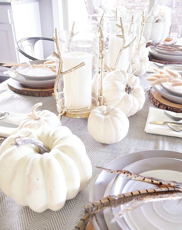 Elegant fall table setting with white pumpkins and gold candles