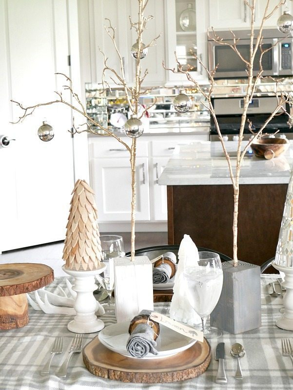 Cozy and Elegant Winter Table Setting with rustic trees and wood rounds