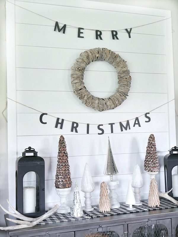 DIY Shiplap Display Wall with a mixture of woodland trees in front! Beautiful natural Christmas Display.