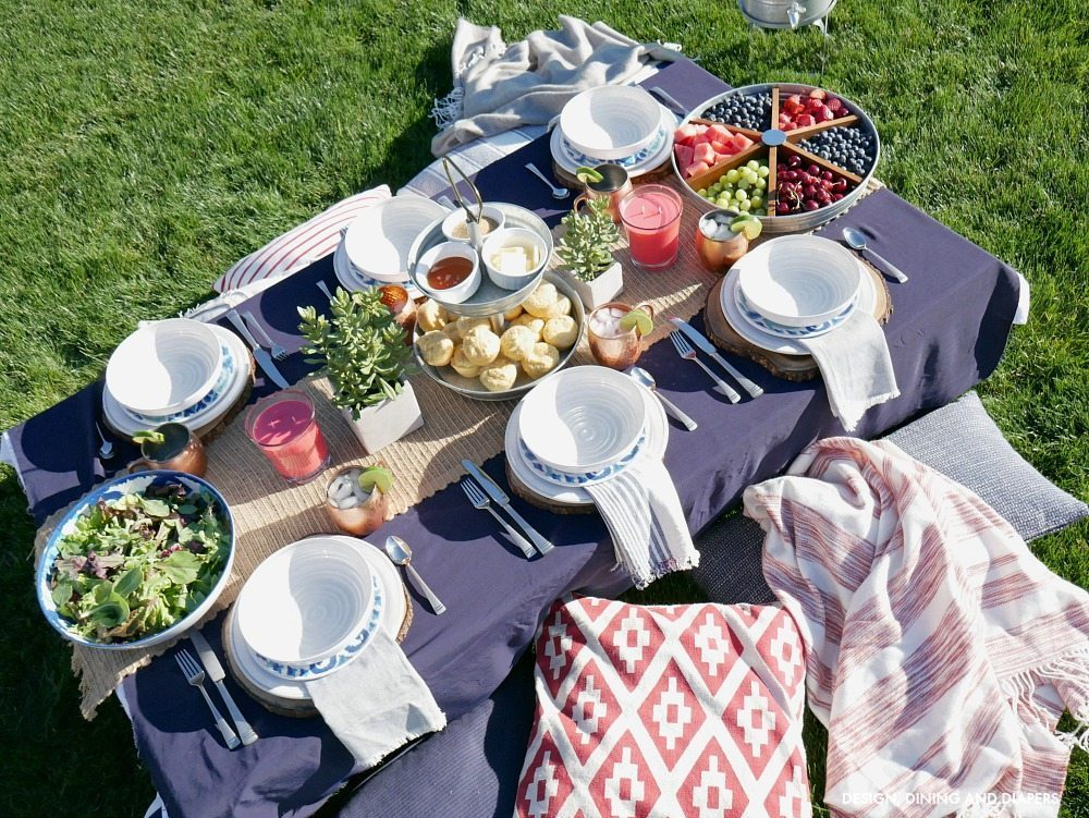 Outdoor navy and red Tablescape with ground seating complete with fluffy pillows and throw blankets