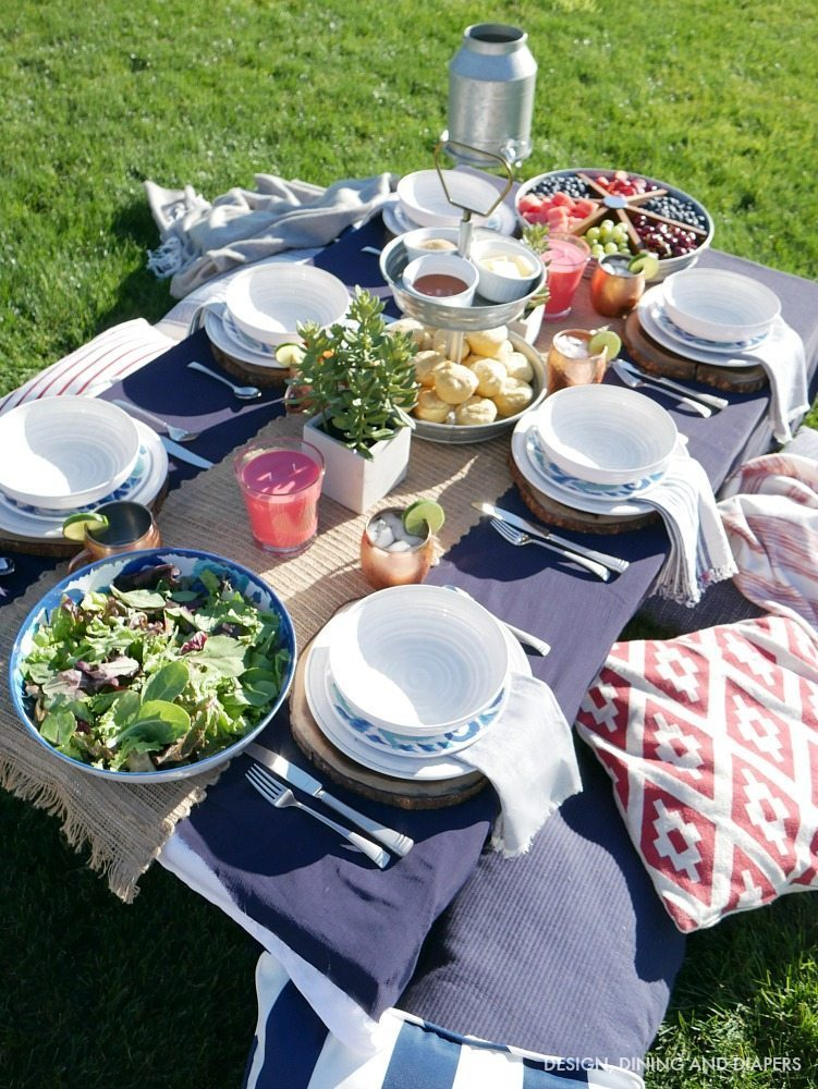 Create a cozy and inviting summer table setting where guests sit on the grass and enjoy a casual environment. This navy and red summer tablescape is full of bright colors and casual touches.