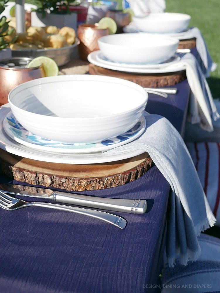 Beautiful outdoor table setting with wood chargers and pretty melamine plates! Keep it casual and chic.