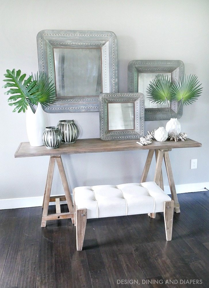 Rustic Chic Entry Way with sawhorse console table and oversized rustic mirror with pops of tropical leaves! Love this look for a classy summer!