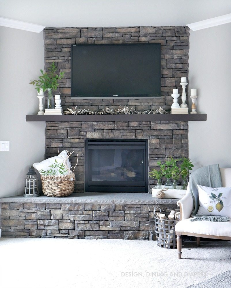 Neutral Summer Mantel with stone fireplace and hearth. Love the touches of soft white candles and books to make it a romantic summer look.