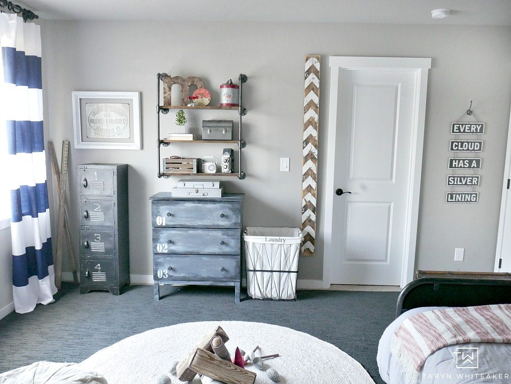 Navy Rustic Boys Room with industrial pipe shelves, wooden growth chart and cute striped curtains!