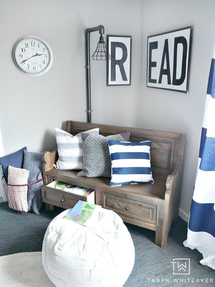An adorable reading nook for a little boys room! Such a cute wooden farmhouse sign with a church pew bench and industrial light!