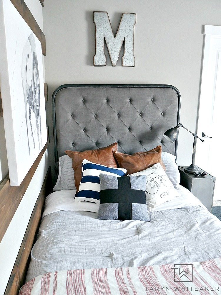 Adorable modern farmhouse bedding for a boy room! Love this oversized gray tufted headboard with leather pillows and lots of texture.