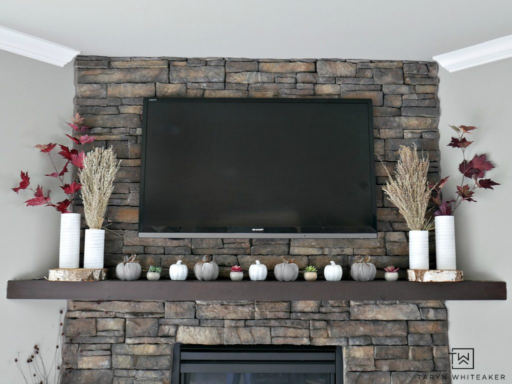 Create a modern boho fall mantel display using a mixture of deep reds, neutrals tones and lots of texture. This is a great look for fall with the earth tones against the stone fireplace.