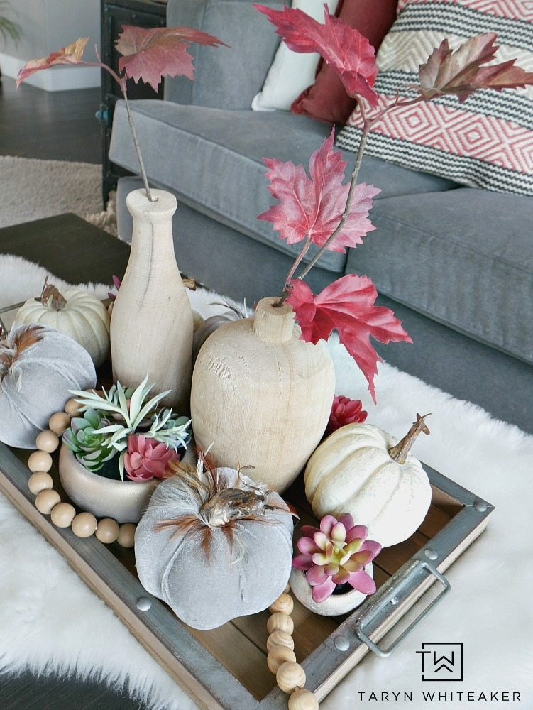 For this piece, it was all about layersing and adding complimentary pieces together to create a Modern Boho Fall Centerpiece. I started with this wood and galvanized tray and built from there. Then, I started to fill it with these beautiful gray velvet pumpkins with feathers, these mini rose gold succulents (which I have fallen in love with), and some white pumpkins.