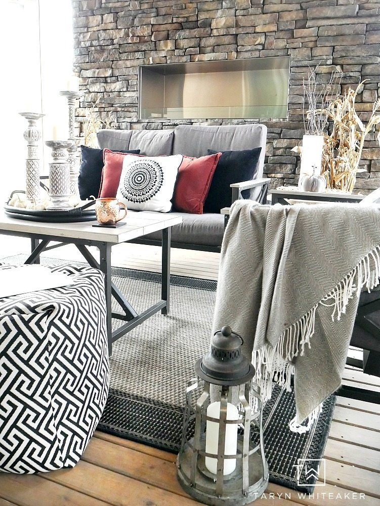 Get cozy in this fall outdoor living space! Taryn used a mixture of black and white with pops of earth tones and texture to create a bold look for fall.
