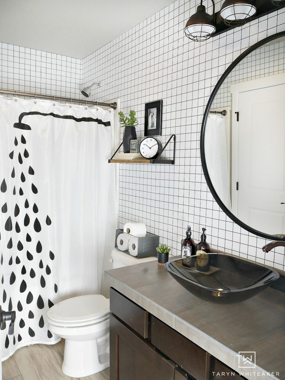Easily transform you boring space into this black and white geometric bathroom using grid patterned wallpaper and modern industrial accents! Click for the before photos, you won't be disappointed!