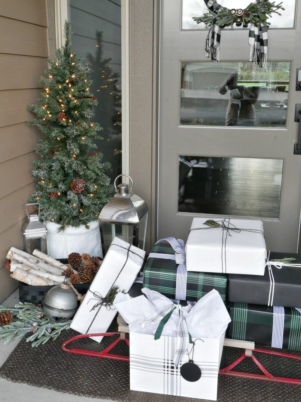 Green and Black Christmas Porch featuring mini trees, a sweater wreath and lots of wintery accents for a festive yet elegant look!