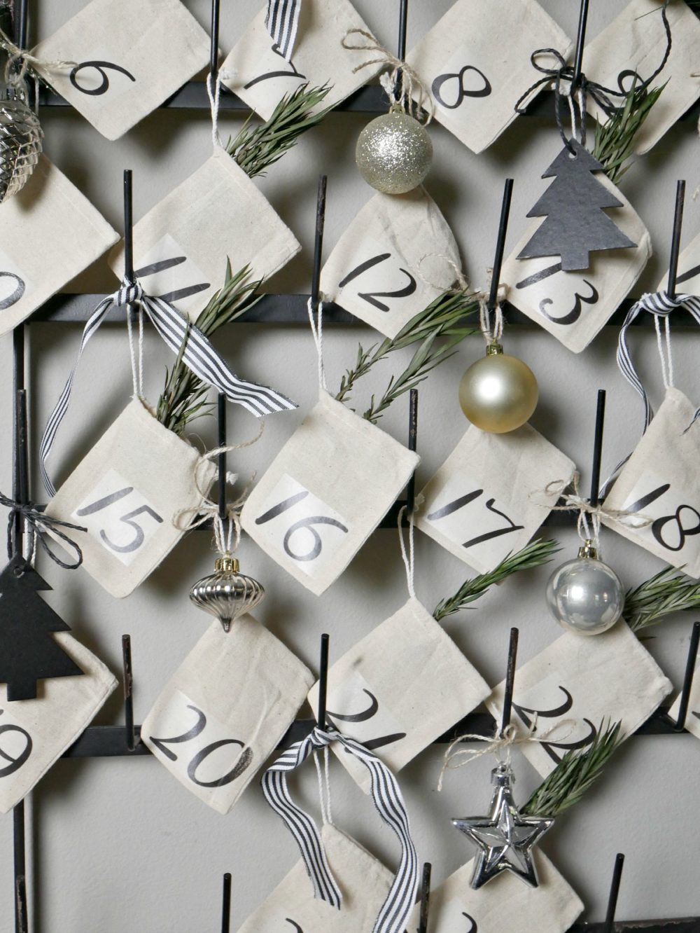Create your own DIY Advent Calendar in less than 30 minutes! These little muslin bags hang perfectly on this vintage bottle drying rack for a festive farmhouse look.
