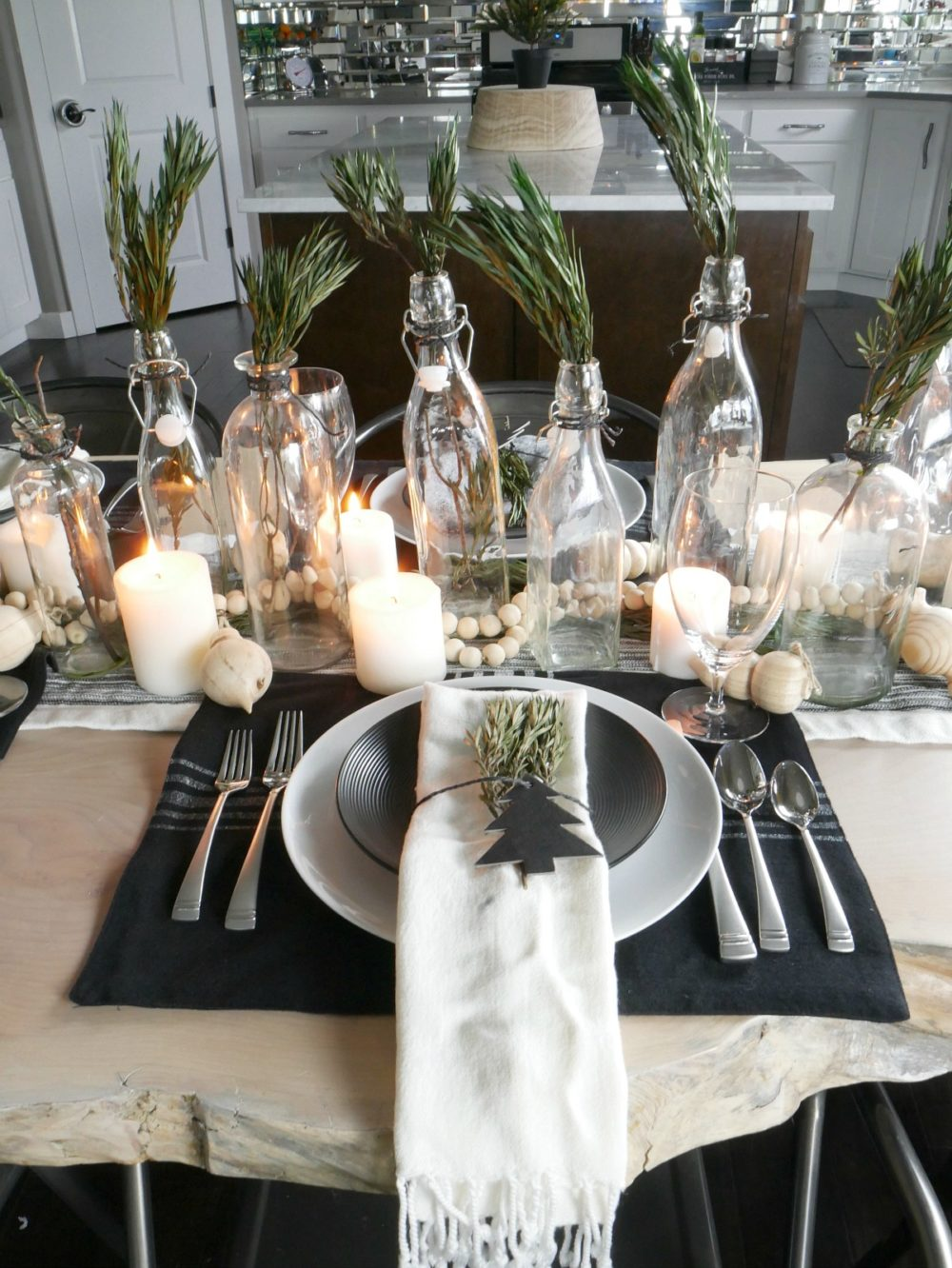 Christmas Table Centerpiece made using glass bottles with sprigs of greenery. The candles next to them give off a pretty glow.