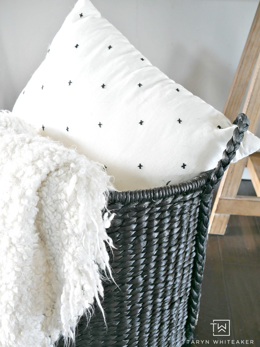 Black whicker basket filled with pops of soft white blankets and pillows.