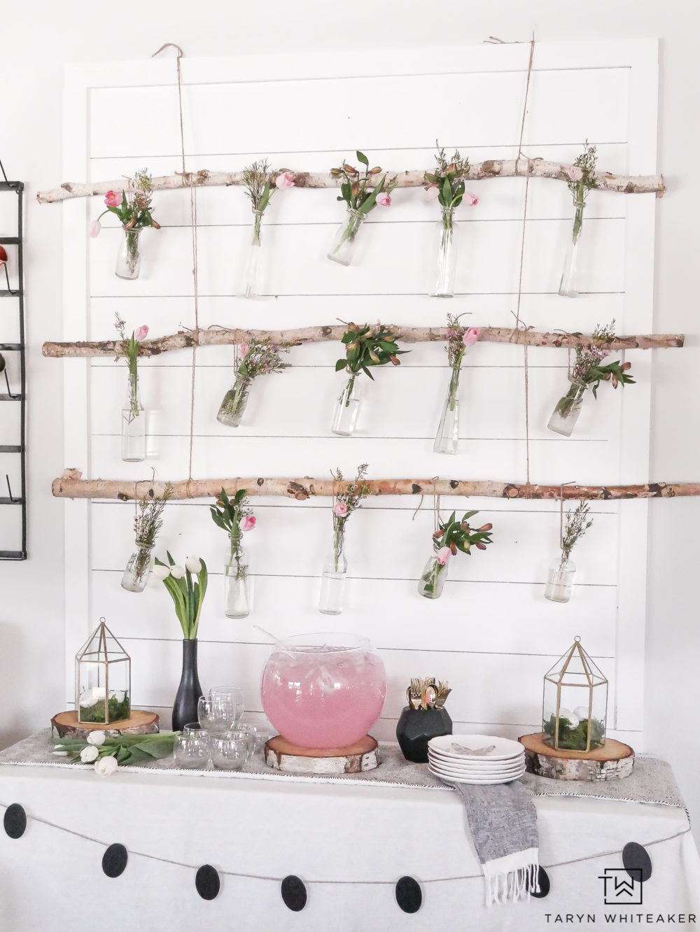 Create this Rustic Hanging Flower Display using birch branches and an eclectic mixture of glass vases! The pink flowers with greenery make it a sweet whimsical flower backdrop for a spring party.