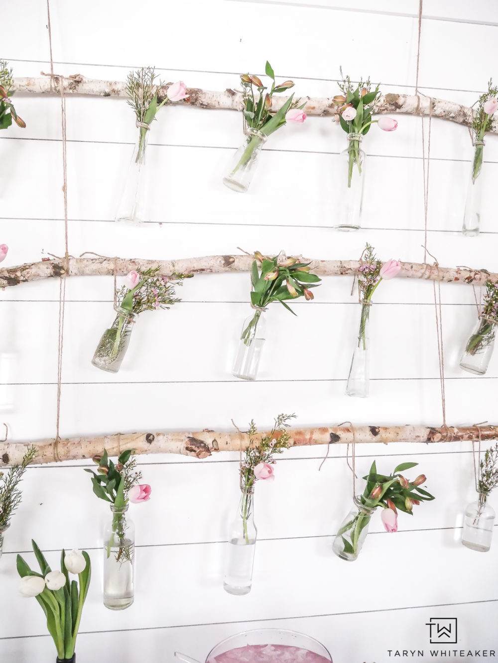 Create this hanging branch floral display using birch branches and fresh garden flowers with pops of pink!