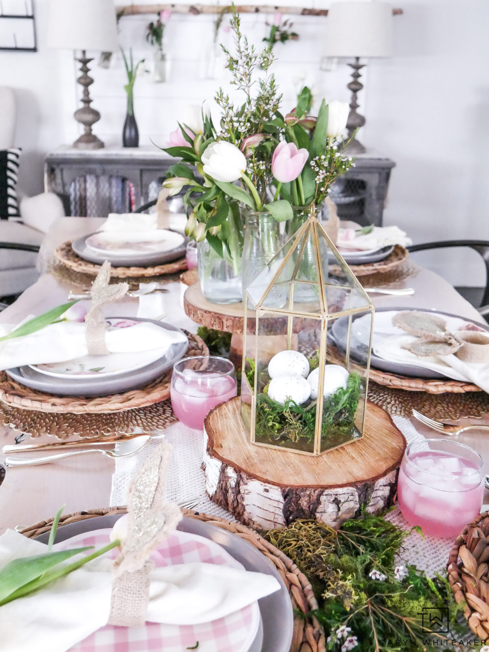 Garden themed Easter table with pink and green accents! Fresh moss centerpiece with wood rounds gives it a rustic touch.