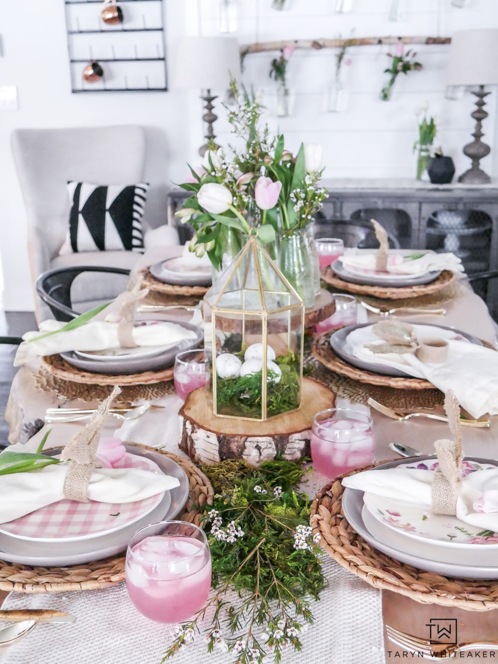 Very enchanting Easter table decor with fresh greenery centerpiece and woodsy touches. The pops of pink make it sweet and charming.