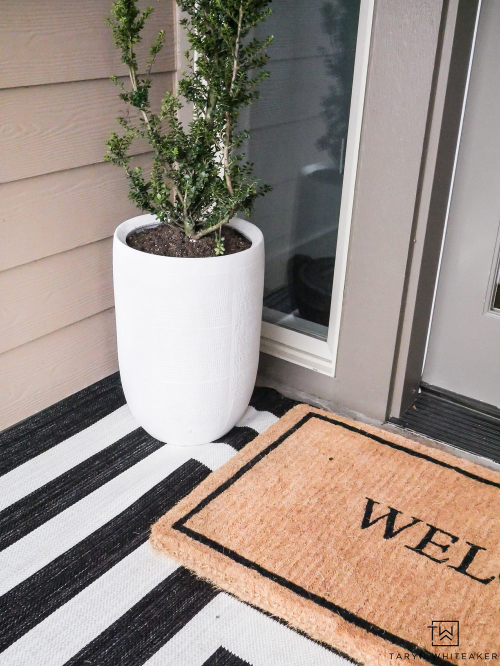 Click to get this Modern Spring Porch Decor look in your own home! The large white planters and layered rugs are simple yet impactful.