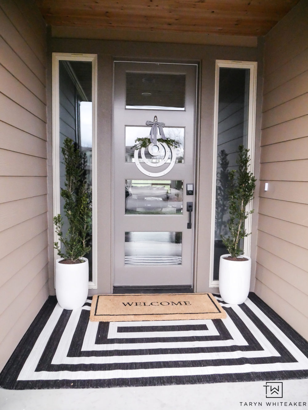 A classic yet modern take on a spring porch! The black and white rug with the modern planters is simple yet so pretty.