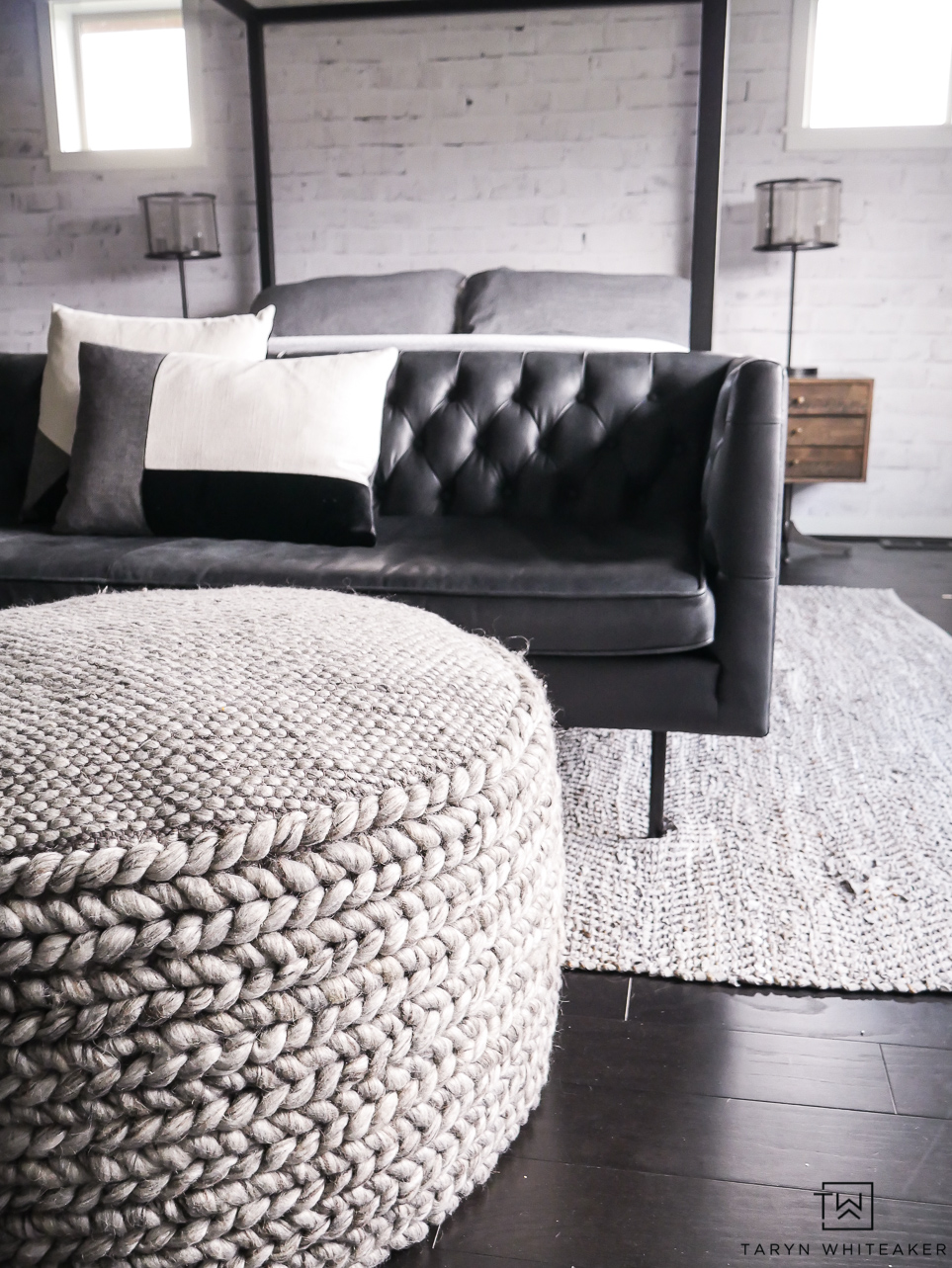 Industrial modern seating area for a bedroom complete with a black leather modern Chesterfield sofa.