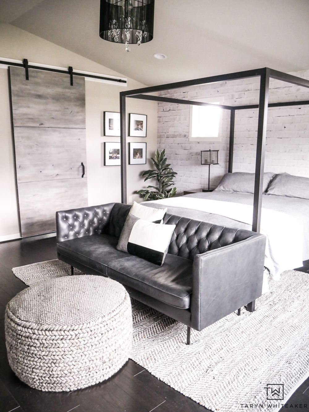 Create a cozy but modern Master Bedroom Seating Area by placing a sofa in front of a canopy and finishing it off with a textured gray ottoman and rug.