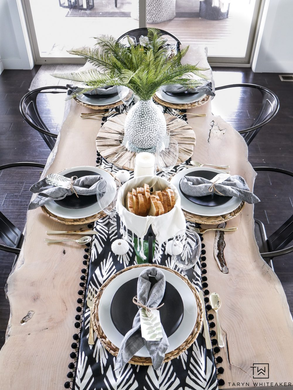 Black and white tropical dinner party decor complete with a DIY boho table runner and pops of tropical leaves.