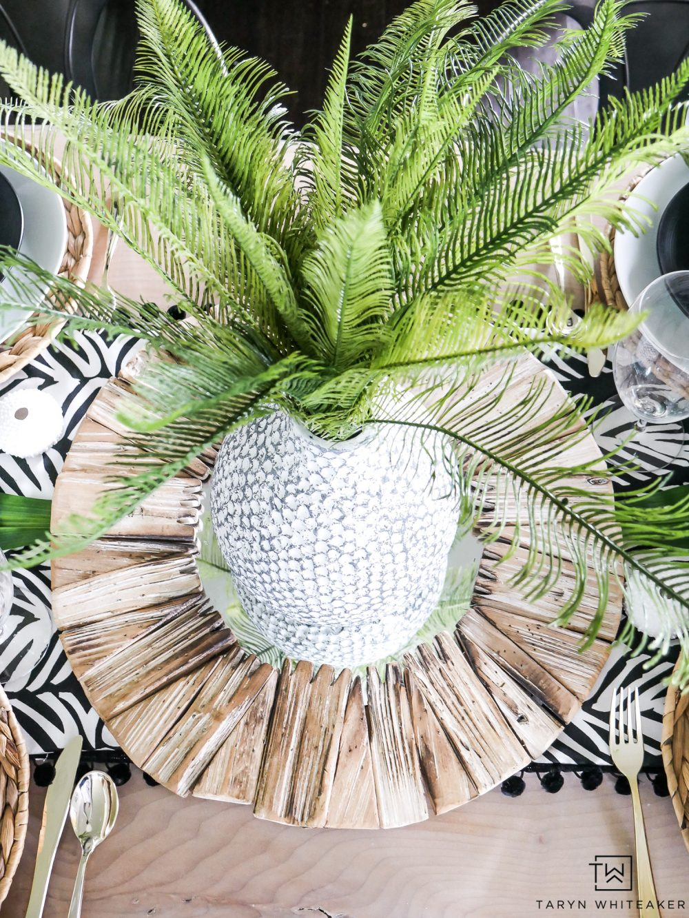 Create a centerpiece using a mirror and vase filled with greenery! A great tropical look for your summer table.