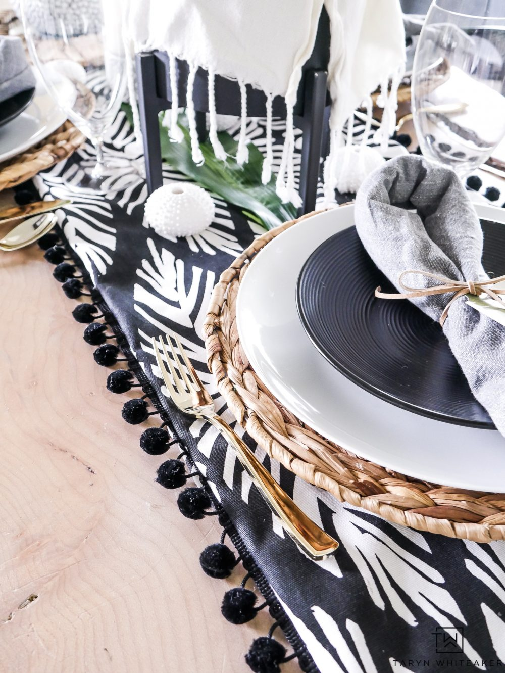 A modern approach to tropical dinner party decor! This black and white tropical table runner with pom pom trim is everything. Love all the coastal elements worked into this
