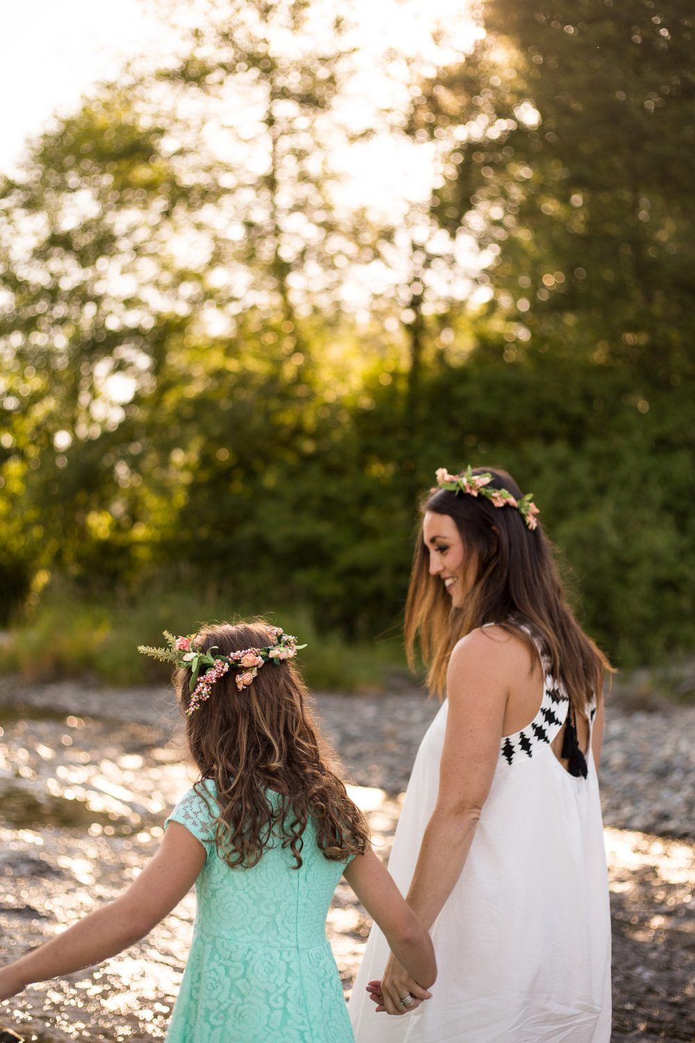 Sweet sunrise photo of mom and daughter with flower crowns.