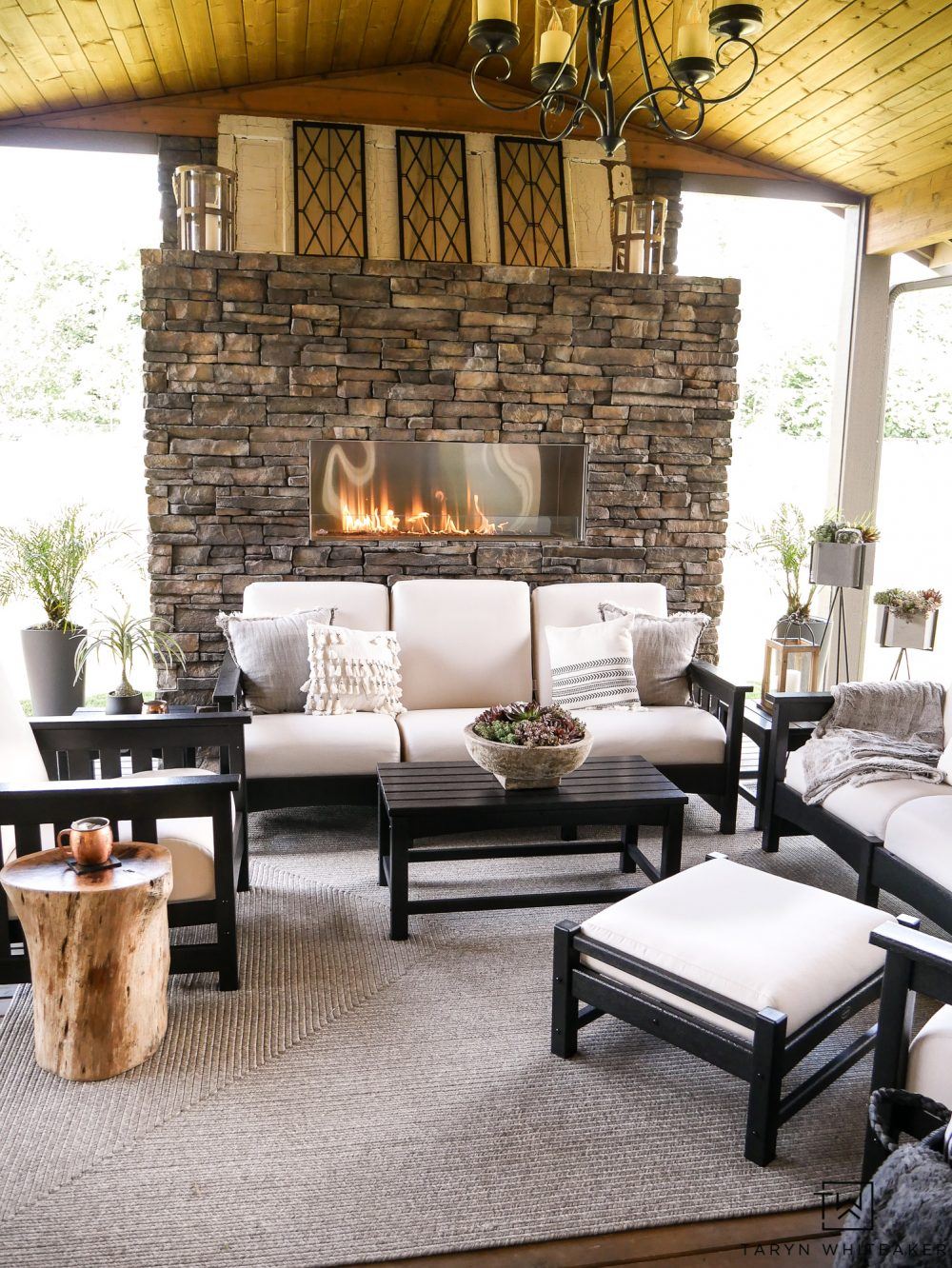 This gorgeous Black and White Outdoor Furniture makes this space feel so luxurious. The neutral tones with the stone fireplace create a soft and cozy living space.