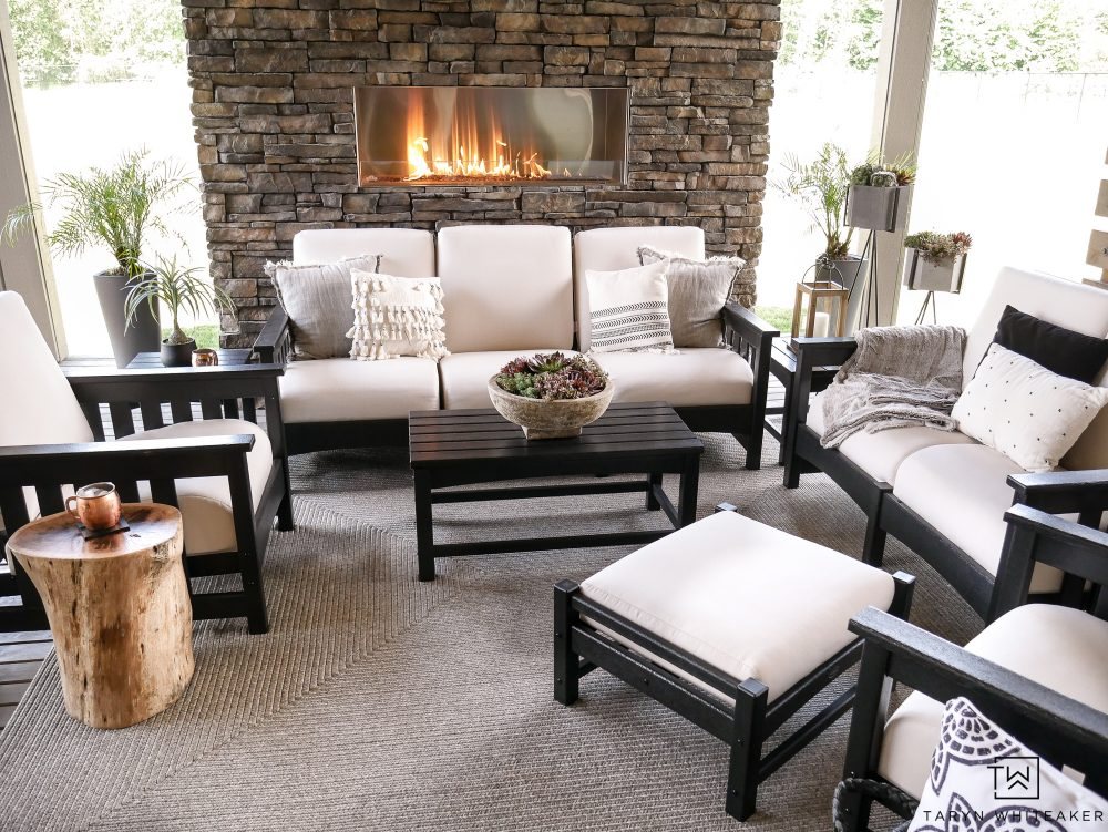Check out this beautiful outdoor living space with black and white outdoor furniture! I love the stone fireplace.