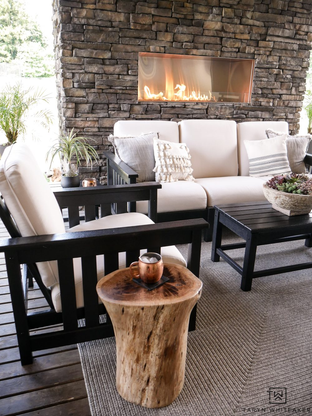 I love this gorgeous outdoor stone fireplace with all the modern furniture pieces. That wood stump side table brings such a great look to the space.