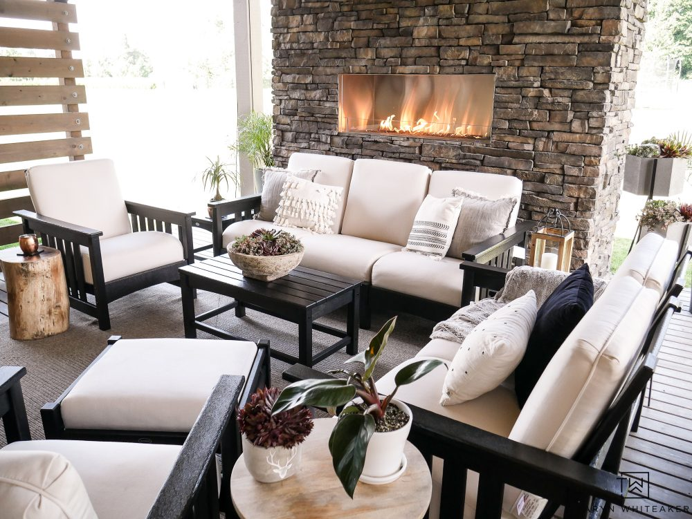 Such a beautiful outdoor living space complete with a stone fireplace and outdoor seating. This black and white furniture set looks so high-end and comfortable!