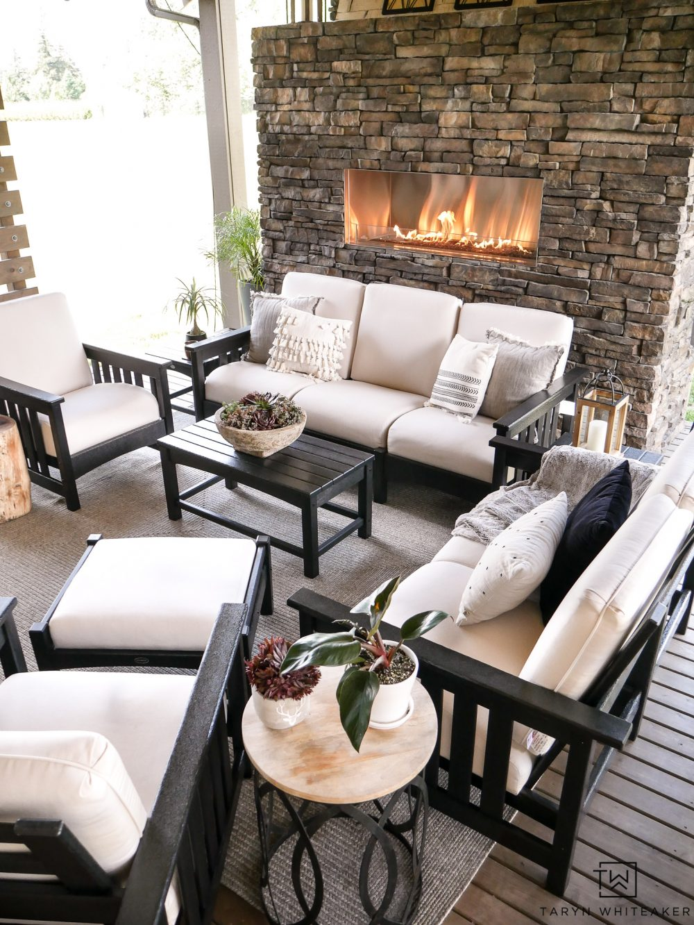 Luxurious outdoor living space with outdoor stone fireplace and beautiful black and white patio furniture.