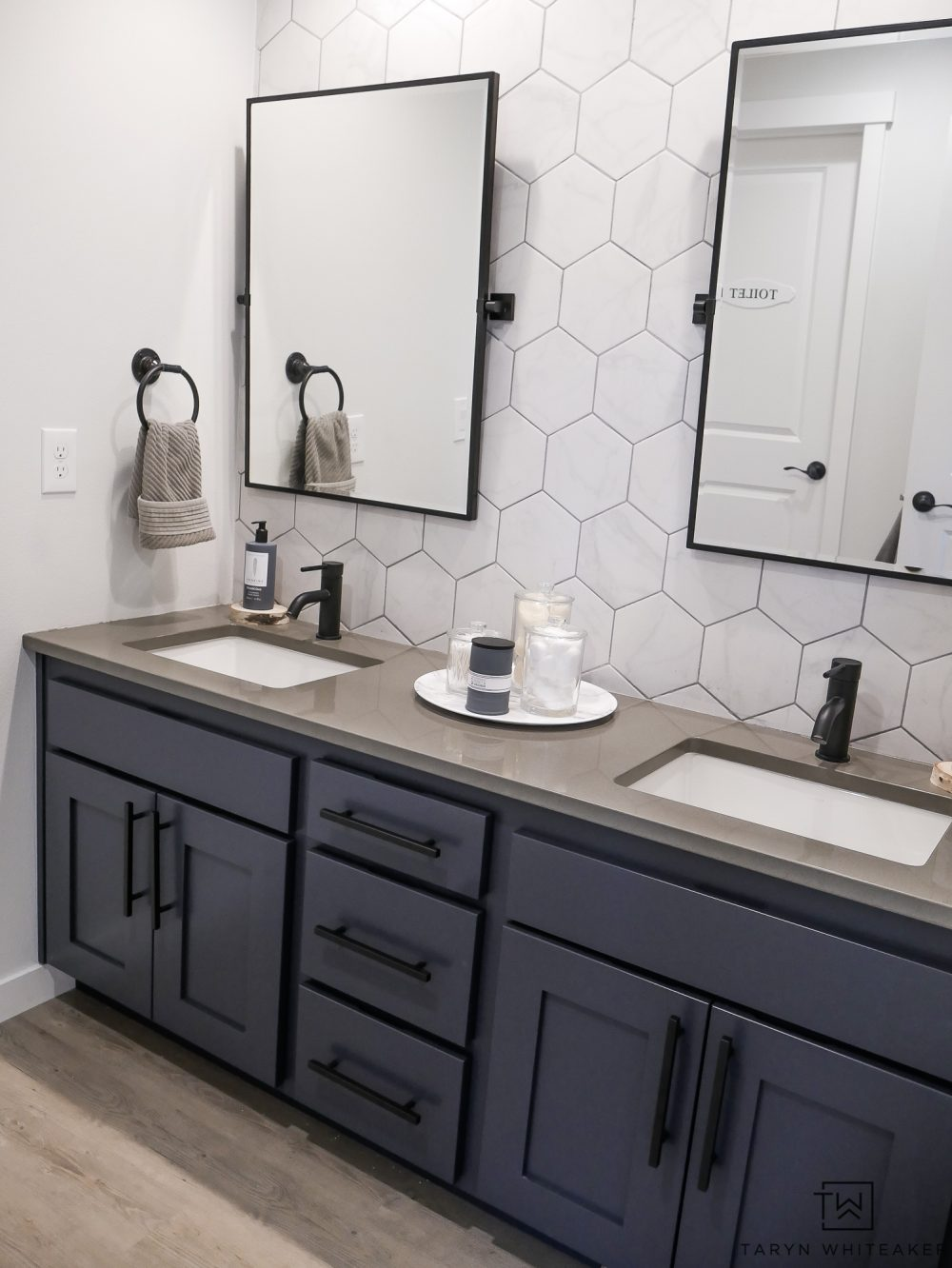 Check out with Kids' Jack-n-Jill Bathroom with a Rustic Modern Look to it with large hexagon tile backsplash, industrial touches and charcoal blue cabinets!