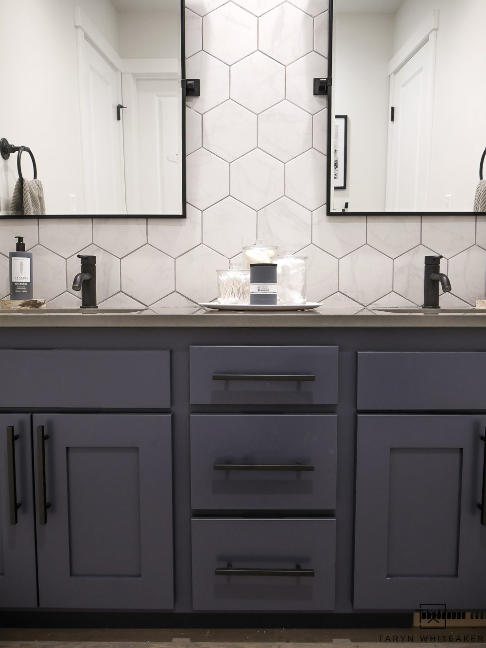 You have to see this bathroom makeover! From basic builder grade to a cool industrial modern bathroom, love the black pivot mirrors paired with the hexagon tile backsplash and charcoal blue cabinets!