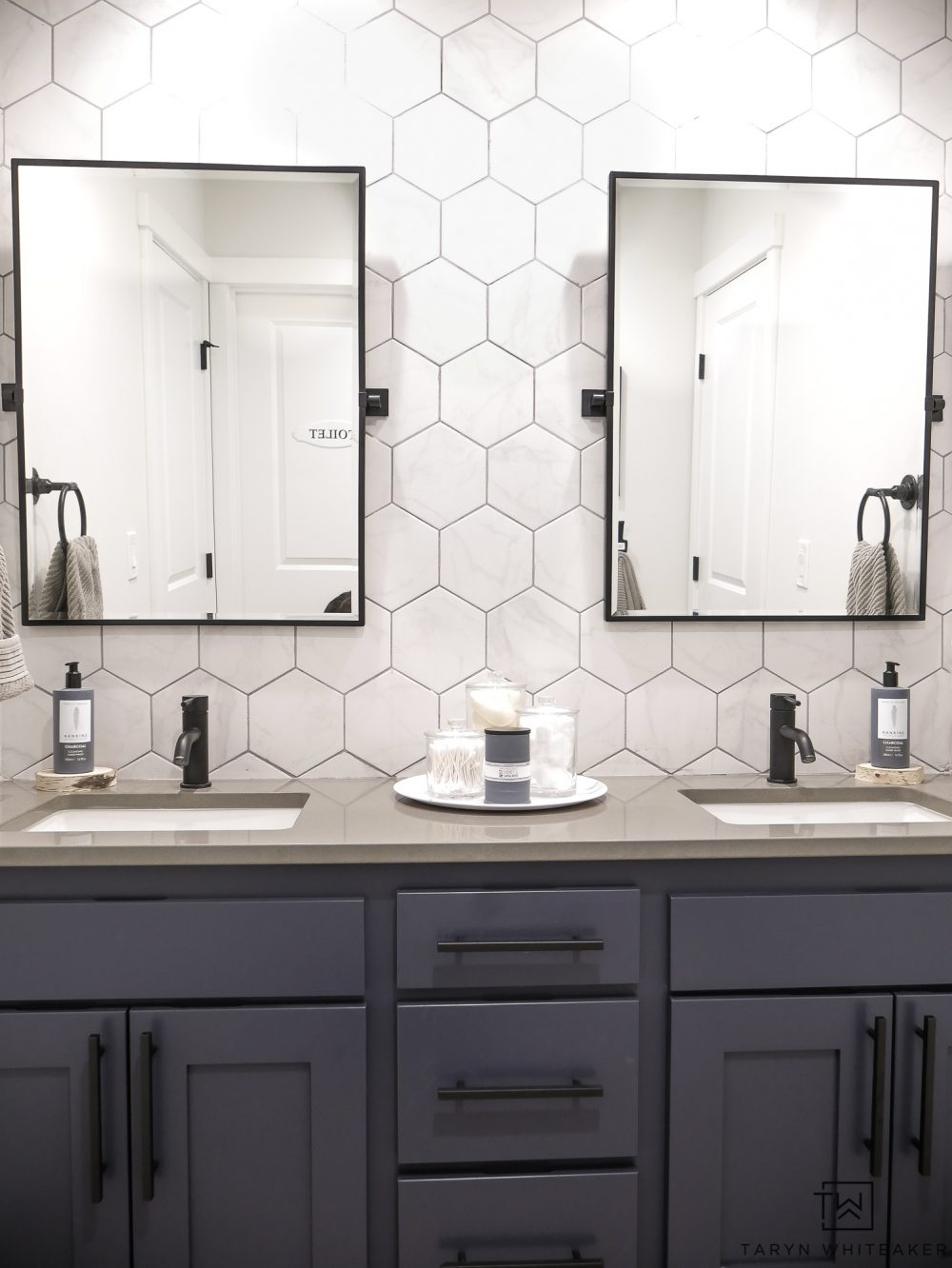 Love this rustic modern double sink vanity bathroom! The full wall backsplash with double mirrors and industrial fixtures has a really unique look.