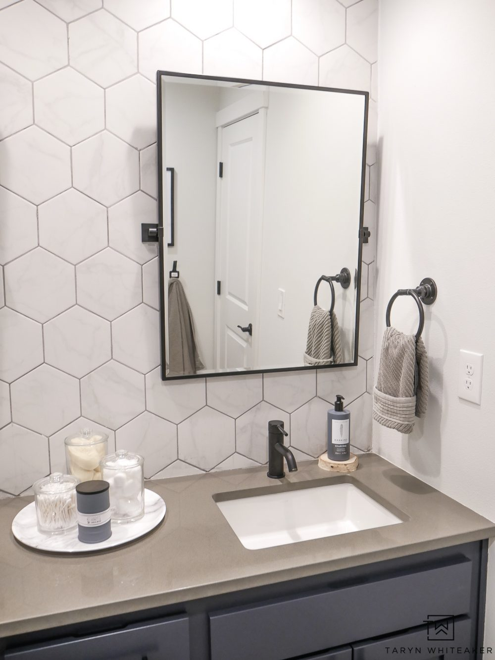 Come see what this bathroom looked like before! This double sink vanity was just a basic builder grade and now it has it's own custom modern look with marble looking hexagon tile, black pivot mirrors and charcoal blue cabinets!