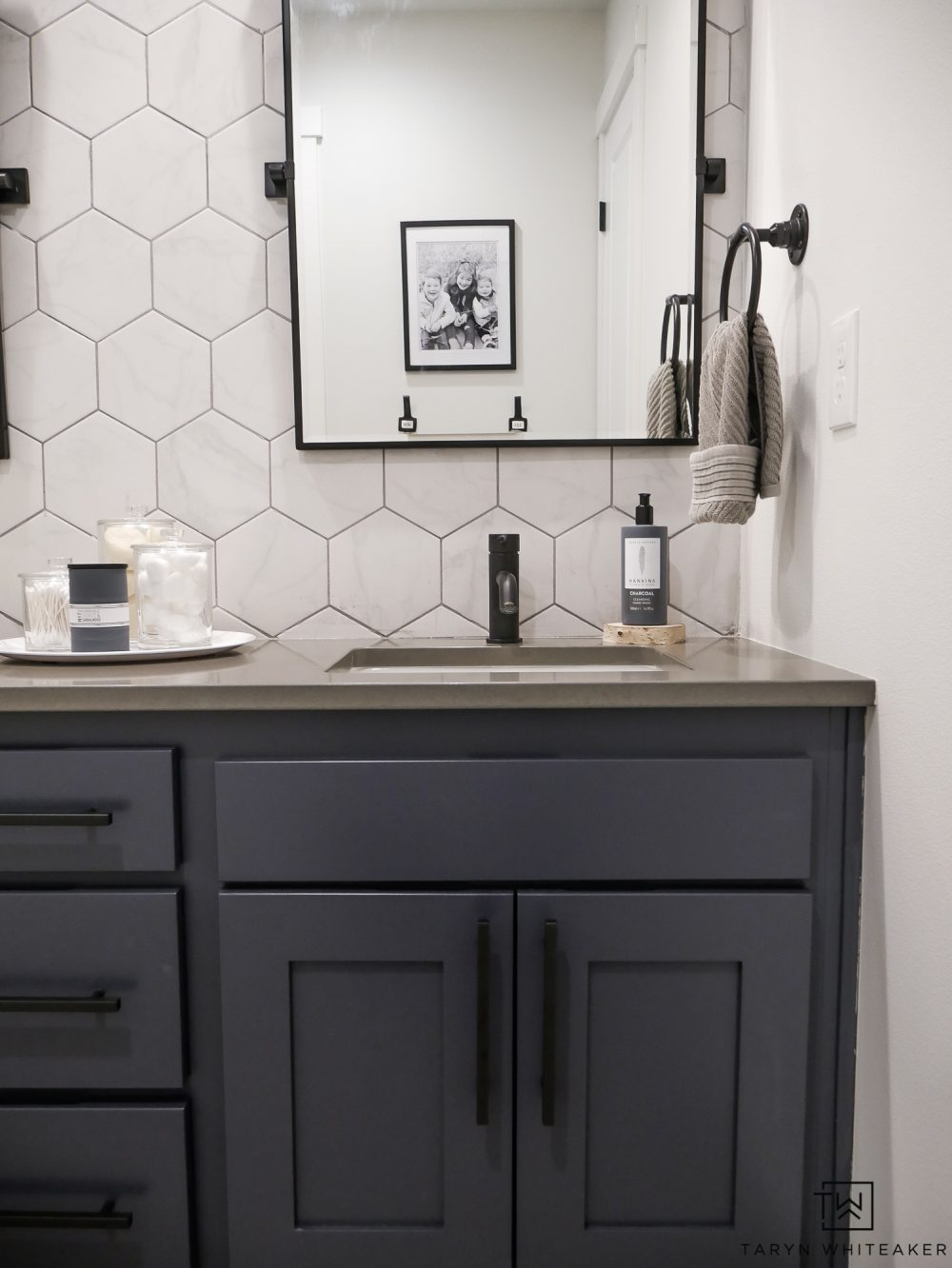 Check out this jack-n-jill bathroom makeover with a rustic modern look! The marble looking hexagon tile makes a huge impact with industrial fixtures.