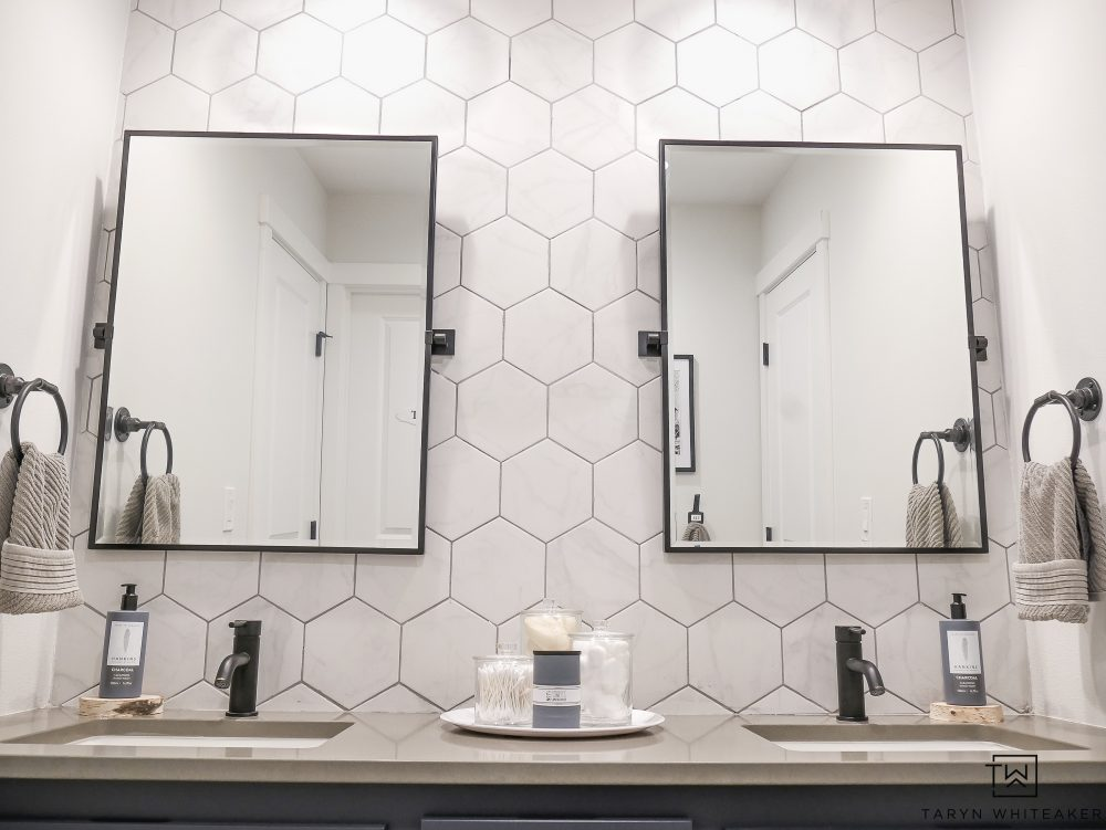 Click to take a look at this full bathroom makeover with black pivot mirrors and white hexagon tile backsplash!