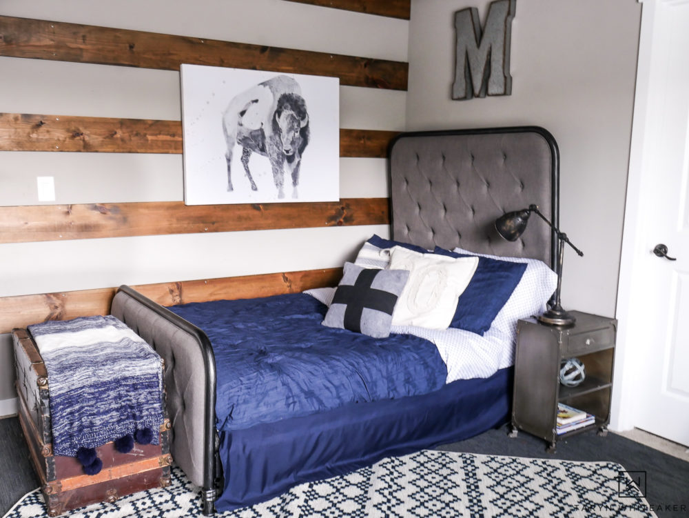 Modern farmhouse boy room design complete with high back headboard, navy blue bedding and patterned rug.