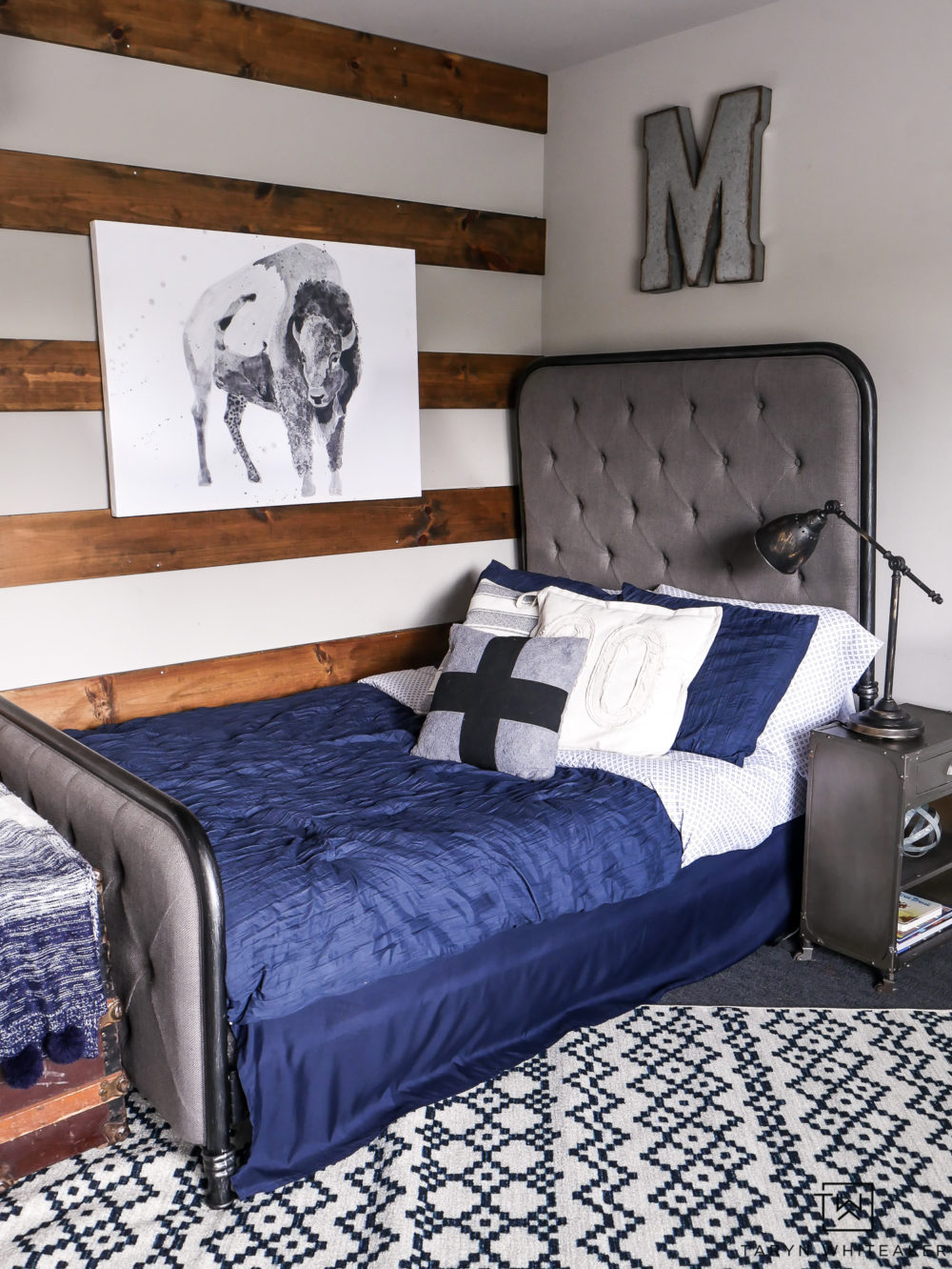 Love this rustic look for a boy room! The navy blue bedding and patterned rug mixed with wood tones and metals.
