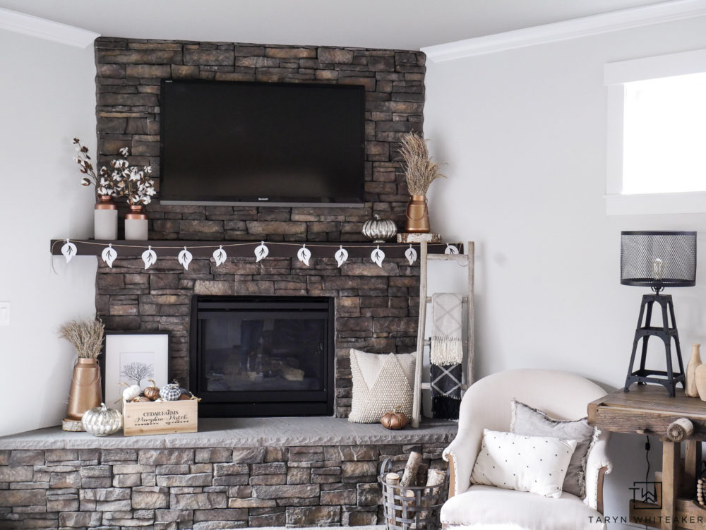 Check out this neutral fall mantel filled with pops of copper and cotton stems. Love all the natural textures against the stone fireplace.