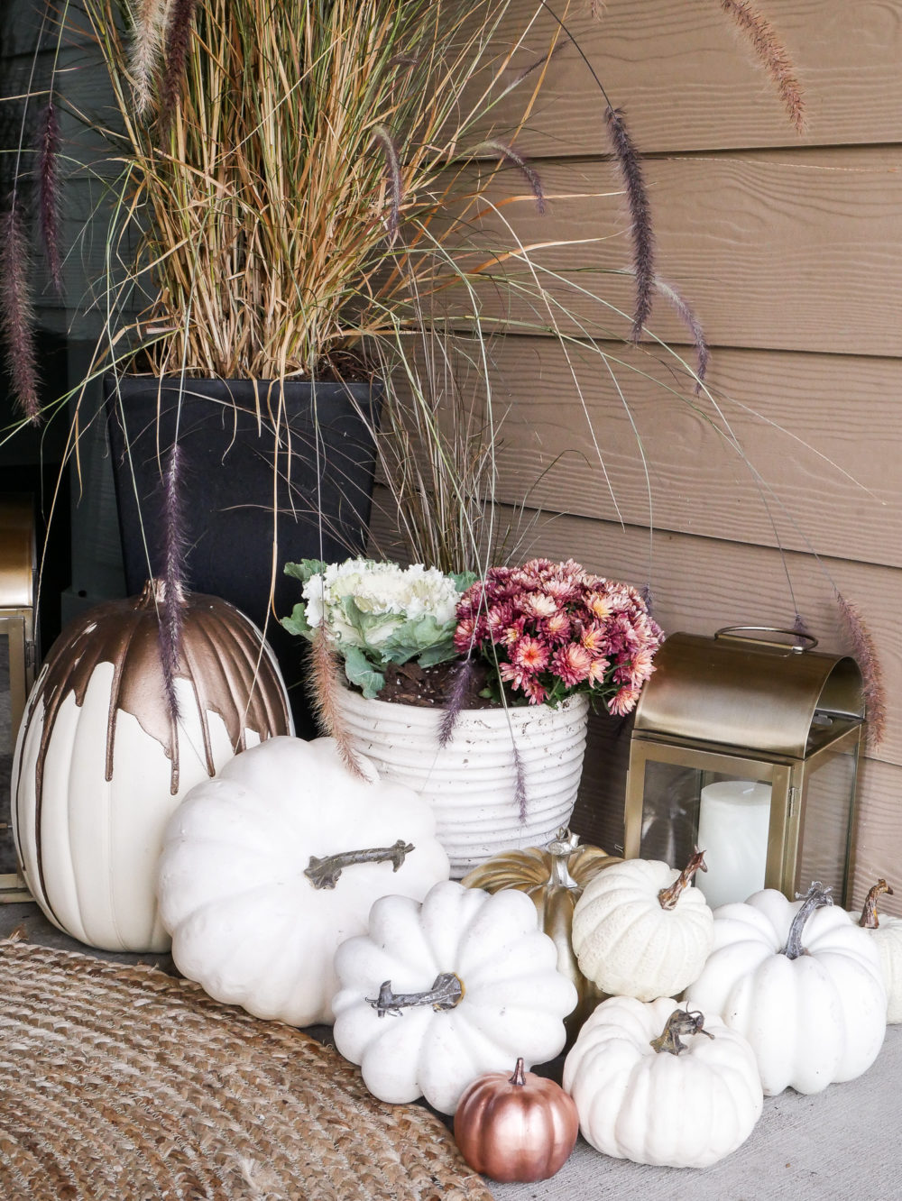 Elegant and classy fall porch featuring white pumpkins and gold lanterns. Those pops of rose gold make this feel so warm and inviting.