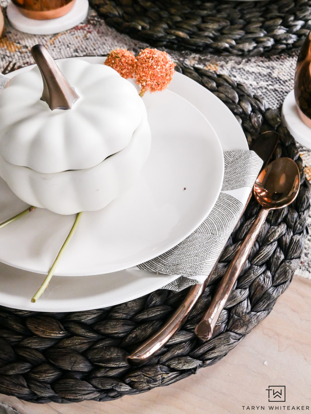 Dark gray, deep orange and modern gray napkins with pops of copper flatware give this fall tablescape a unique and traditional look at the same time.