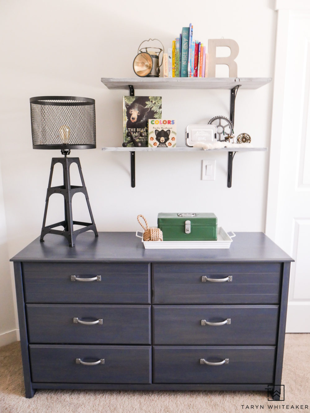 Navy blue dresser with open shelving for a boys room.